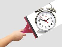 Hand washes the alarm clock. On grey background Stock Photos