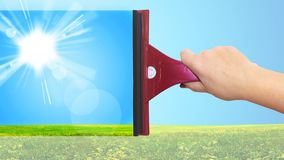 A hand washes the blue sky. And a green field Stock Photos