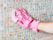 Hand washes ceramic tiles on kitchen wall stock photography