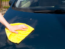 The hand washes a rag the car. The hand washes a yellow rag the car Stock Photo