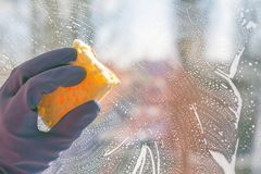 Hand washes window World Cleanup Day. Hand blue glove washes window with yellow sponge. World Cleanup Day concept, copy space, close up, selective focus royalty free stock images