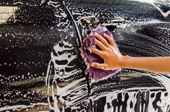 Hand washing a car with a microfiber cloth Stock Photos