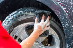 Hand washing car tire  with black sponge Stock Photos