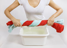 Hand washing of color laundry. Woman with color towels in her hand Stock Images