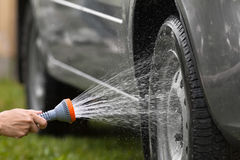 Hand washing grey car with flowing water Royalty Free Stock Image