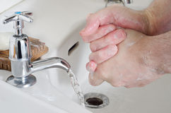 Hand Washing - Male. Male hands being washed in old china sink with water running from stainless steel tap, and a bar of soap resting on a wooden soap dish Stock Photos