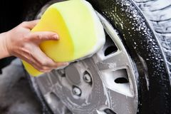 Hand washing a tire with sponge Stock Image