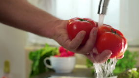 HAND WASHING TWO TOMATOES UNDER A FLUSH OF WATER. DOLLY SHOT. CAUCASIAN HANDS WASHING TWO TOMATOES UNDER A FLUSH OF WATER. TAKES IT OUT OF THE FRAME. DOLLY SHOT stock video footage