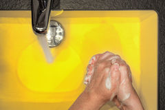 Hand washing in yellow. Girl hand washing her hands in a yellow colored washbasin Stock Photo