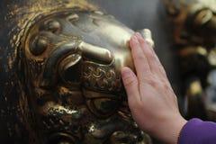 Hand wat betreft het hoofd van de bronsleeuw Royalty-vrije Stock Afbeeldingen