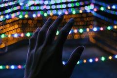 Hand wat betreft kleurrijke bokehlichten met goed gevoel Royalty-vrije Stock Foto