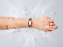Hand with watch and numbers on the side comming out Royalty Free Stock Photos