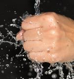 Hand in water on a black background.  Stock Images