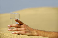 Hand with water in desert Stock Images