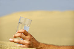 Hand and water in desert Royalty Free Stock Photos