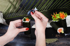 Hand watering soy sauce sushi roll crab meat salmon cucumber Stock Photos