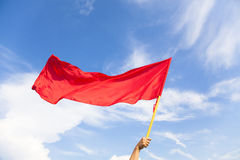 Hand waving a red flag with blue sky background Royalty Free Stock Photography