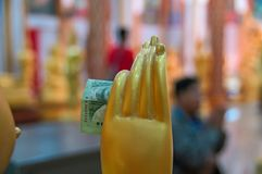 In hand of the wax statue of a Buddhist monk inserted donation banknote. Concept of religious donations alms in Buddhist temple. In the hand of the wax statue royalty free stock images