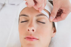 Hand waxing beautiful woman's eyebrow Stock Photos