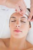 Hand waxing beautiful woman's eyebrow Royalty Free Stock Images