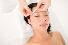 Hand waxing beautiful womans eyebrow. Close up view of hands waxing beautiful womans eyebrow royalty free stock photo