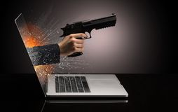 Hand with weapon coming out of a laptop royalty free stock photos