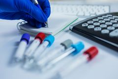 Hand wearing blue gloves making notes next to bottles for samples used in hospitals or medicine for blood samples in a royalty free stock image