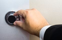 Hand wearing business suit turning safe dial lock.  Stock Photography
