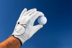 Hand wearing golf glove holding a white golf ball Stock Photo