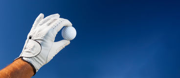 Hand wearing golf glove holding a white golf ball Stock Images