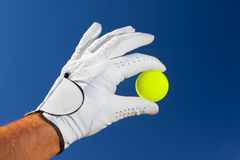Hand wearing golf glove holding a yellow golf ball Stock Photography