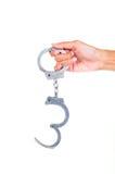 Hand wearing handcuffs Stock Photo
