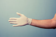 Hand wearing latex glove offering handshake Stock Image