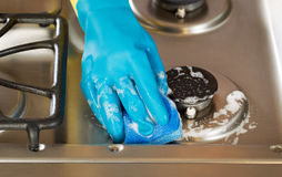 Hand wearing rubber glove while cleaning stove top range with s. Closeup horizontal image of hand wearing rubber glove while cleaning stove top range with soapy Stock Image