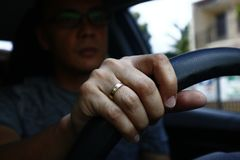 Hand with wedding ring of an Asian man inside a car holding the steering wheel stock photos