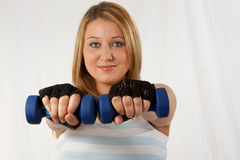 Hand weights. Attractive blond caucasian woman wearing workout attire with hands forward holding two three pound blue weights focus on hands stock photography