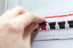Hand, welche die automatischen Schalter des Stroms im elektrischen Schild des Hauses - Strombedienfeld mit Stromkreis schaltet lizenzfreies stockbild