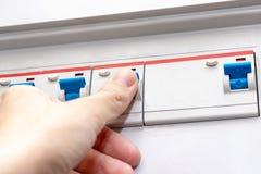 Hand, welche die automatischen Schalter des Stroms im elektrischen Schild des Hauses - Strombedienfeld mit Stromkreis schaltet stockbild