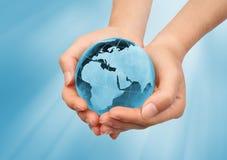 Hand, welche die blaue Erde anhält Lizenzfreies Stockbild