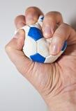 Hand, welche die Druckkugel zusammendrückt Lizenzfreie Stockfotografie