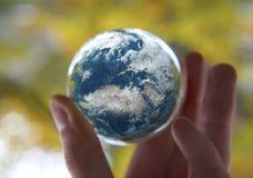 Hand, welche die Erde mit Herbsthintergrund hält lizenzfreie stockfotografie