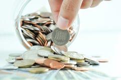 Hand, welche die 100-japanischer Yen-Münze aufhebt Stockfoto