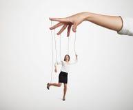 Hand, welche die kleine Marionette manipuliert Stockfoto
