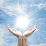 Hand, welche die Sonne anhält stockbild