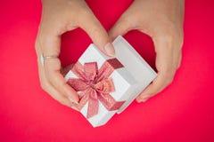 Hand, welche die weiße Geschenkbox, benutzt für den Silvesterabend, Weihnachten, Geburtstag, Valentinstag hält auf redbackground lizenzfreie stockfotos
