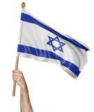 Hand, welche stolz die Staatsflagge von Israel wellenartig bewegt stockbilder