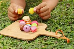 Hand were picked colorful of macaron on a brown tray Royalty Free Stock Images