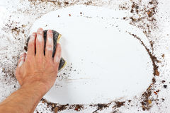 Hand with wet black sponge wiping heavily dirty surface Royalty Free Stock Photography