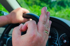 Hand on the wheel, sign OK. Hand on the wheel, the other hand shows the OK sign Royalty Free Stock Photos