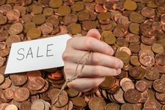 The hand which is sticking out of heap of coins with sales tag.Copy space stock photos